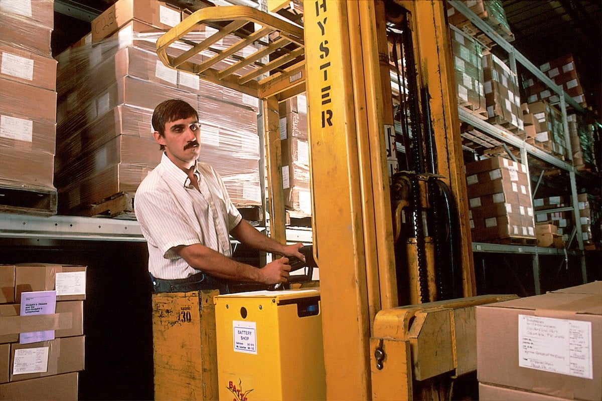 Forklift operator in industrial warehouse
